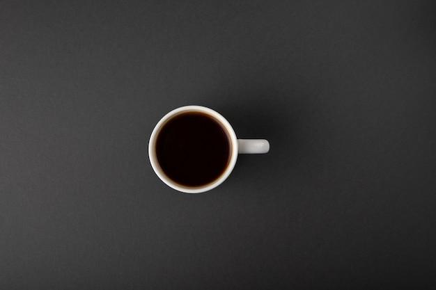 Koffiekop op grijs wordt geïsoleerd die