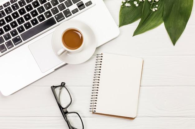 Koffiekop op laptop, oogglazen, spiraalvormige blocnote en bladeren op wit bureau