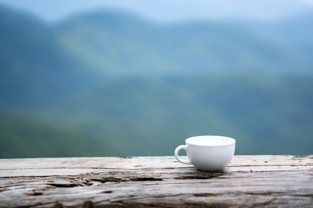 Koffiekop op oud hout op aardmening van mist op berg en blauwe hemel en wolk