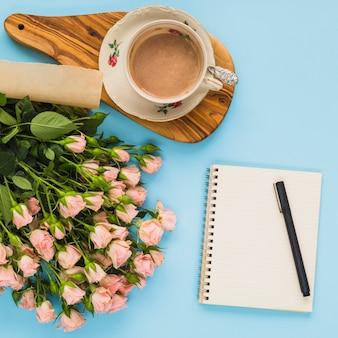 Koffiekop; roze rozen; spiraal notitieblok; pen op blauwe achtergrond