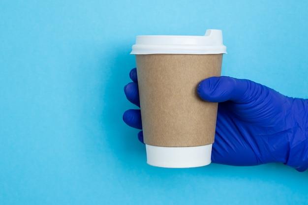 Koffiekop ter beschikking geïsoleerd op blauwe achtergrond. hand met papieren beker.