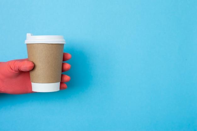 Koffiekop ter beschikking met beschermende handschoenen die op blauwe achtergrond worden geïsoleerd. hand met papieren beker.