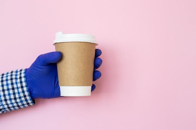 Koffiekop ter beschikking met medische handschoenen die op blauwe achtergrond worden geïsoleerd. hand met papieren beker, coronavirusbescherming
