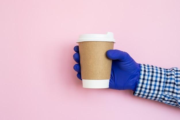 Koffiekop ter beschikking met medische handschoenen die op blauwe achtergrond worden geïsoleerd. vrouwelijke hand met papieren beker.