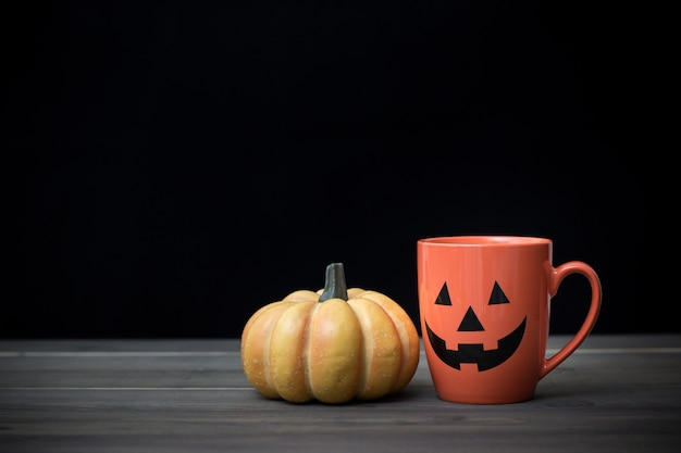 Koffiekopje als jack o lantern pompoen op houten tafel. halloween-concept