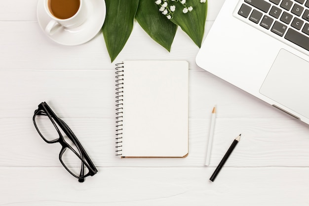Koffiekopje, bladeren, spiraal kladblok, brillen op kantoor houten bureau