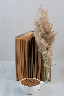 Koffiekopje, boek en plant op grijze tafel. hoge kwaliteit foto