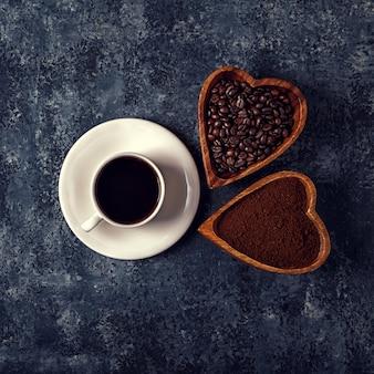Koffiekopje, bonen en gemalen poeder op stenen tafel.