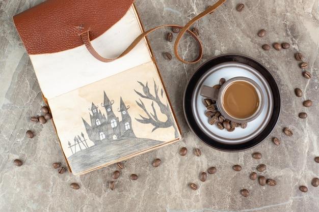 Koffiekopje, bonen en notitieboekje op marmeren oppervlak