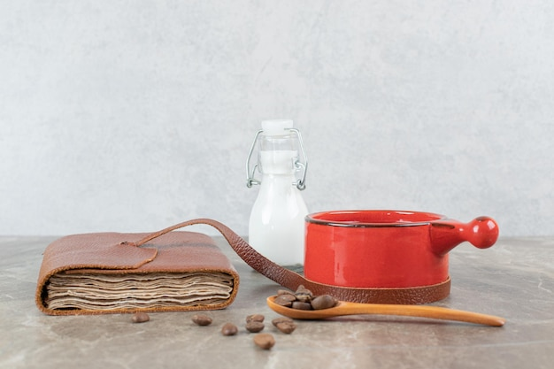 Koffiekopje, bonen en notitieboekje op marmeren tafel.