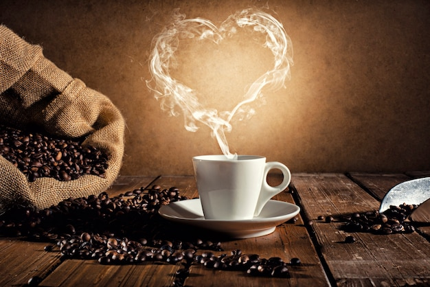 Koffiekopje boven een houten tafel met een rook in de vorm van een haard