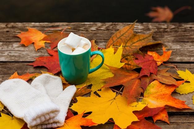 Koffiekopje cappuccino en herfstbladeren met wanten en marshmallows in het oppervlak van oude donkere houten vloerdelen.