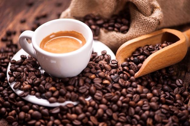 Koffiekopje close-up over donkere gebrande koffiebonen