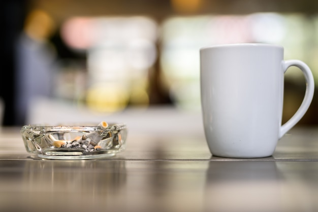 Koffiekopje en asbak met sigaretten op houten tafel in restaurant