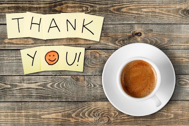 Koffiekopje en bedankje op houten achtergrond