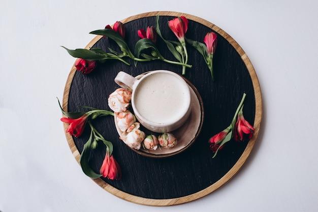 Koffiekopje en bloemen op donkere houten tafel in café