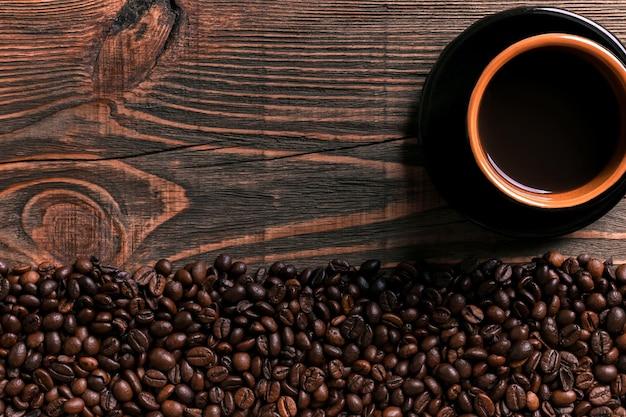 Koffiekopje en bonen frame op houten tafel. bovenaanzicht. ruimte kopiëren. stilleven. mock-up. plat leggen