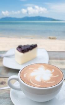 Koffiekopje en cake op terras met uitzicht op zeegezicht