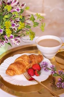 Koffiekopje en croissant met verse aardbei op gouden plaat