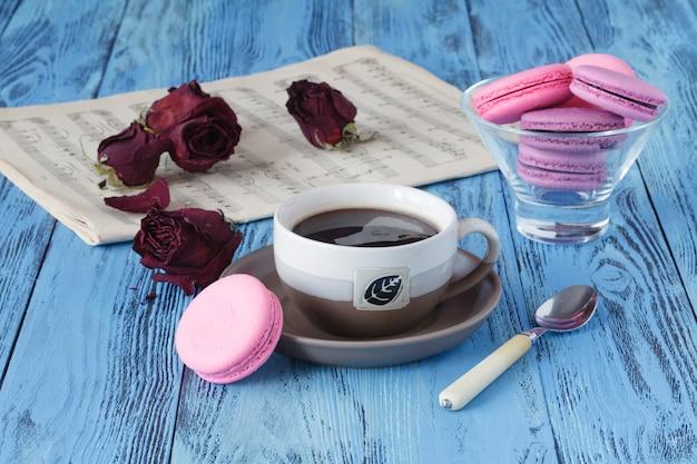 Koffiekopje en gedroogde rode roos op houten tafel