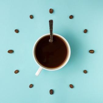 Koffiekopje en geroosterde bonen gerangschikt als wijzerplaat, bovenaanzicht. koffietijd. interessant idee energie en verfrissing concept.