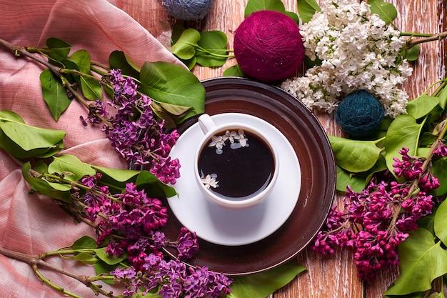 Koffiekopje en kleurrijke lila bloemen op houten tuintafel