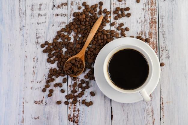 Koffiekopje en koffiebonen in houten lepel op witte tafel.
