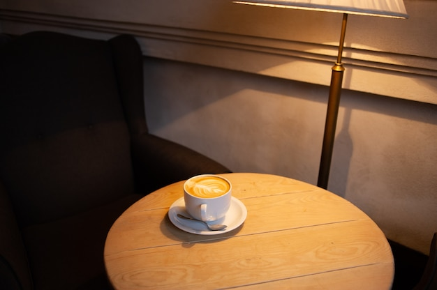 Koffiekopje en koffiebonen op houten tafel. latte in een witte kop in een café