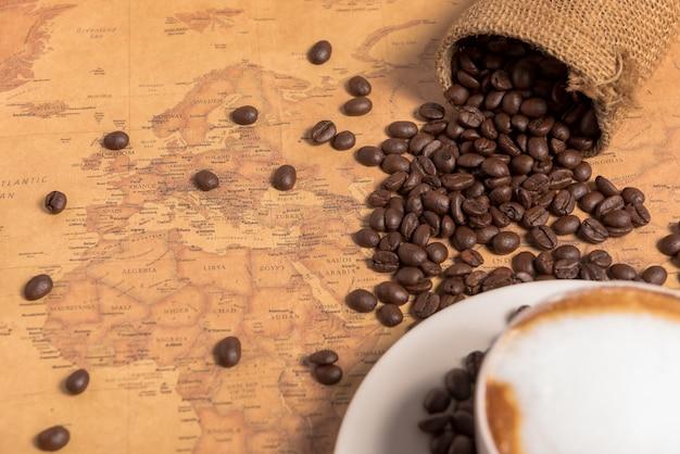 Koffiekopje en koffiebonen op tafel met grote kaart achtergrond op tabblad tabel