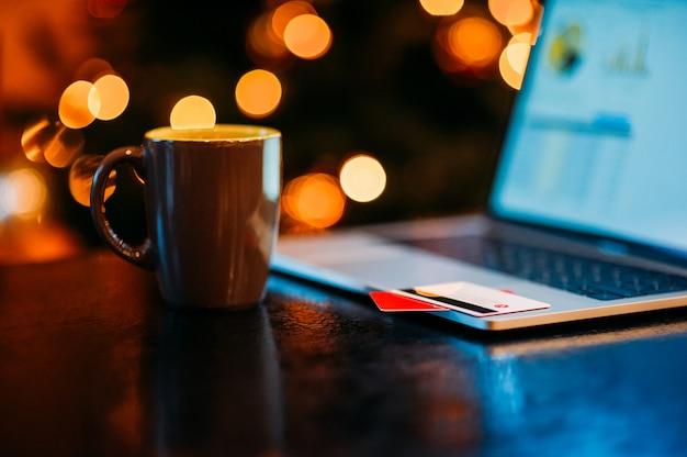 Koffiekopje en laptop op kerstdecoratie