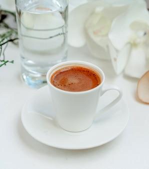 Koffiekopje en nog steeds water op de tafel