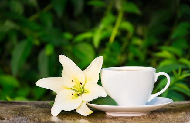 Koffiekopje en witte lelie op natuurlijke groene achtergrond.