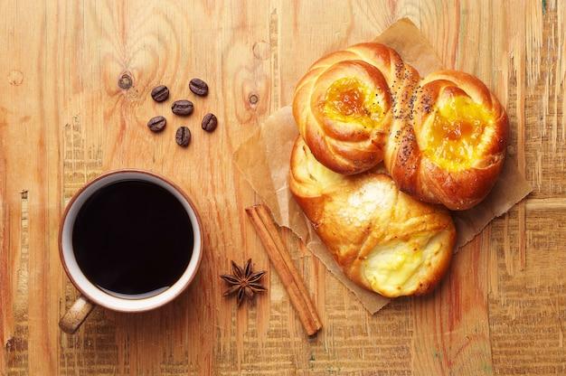 Koffiekopje en zoete broodjes op oude houten tafel