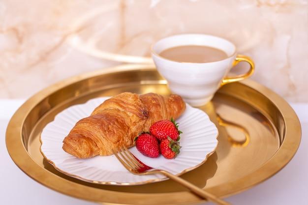 Koffiekopje en zoete croissant met verse aardbei op gouden plaat