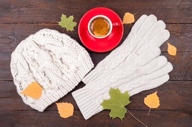 Koffiekopje, handschoenen, handgemaakte gebreide muts en herfstbladeren op houten planken