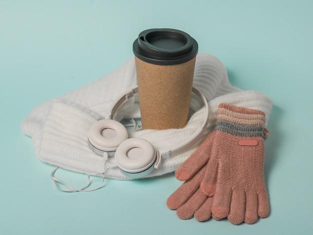 Koffiekopje, handschoenen, sjaal en koptelefoon. winterstemming.