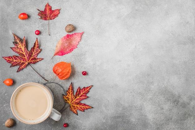 Koffiekopje, herfstbladeren, bloemen, bessen en noten
