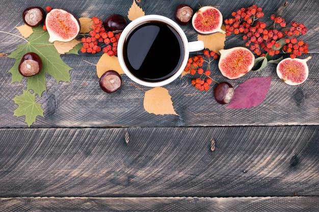 Koffiekopje, herfstbladeren en gedroogde lijsterbes op houten achtergrond
