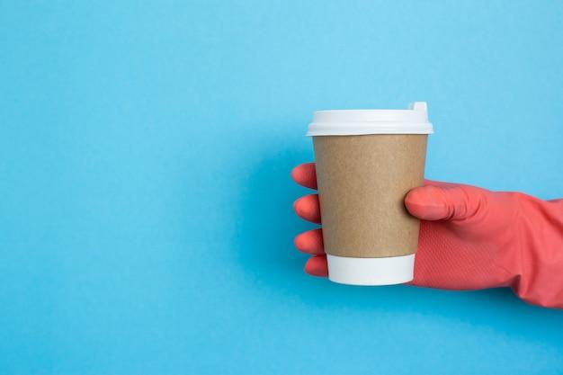 Koffiekopje in de hand met roze medische handschoenen geïsoleerd op blauwe achtergrond. vrouwelijke hand met papieren beker. mockup van vrouwelijke hand met een kopje koffie beker. kopieer ruimte. coronavirus bescherming