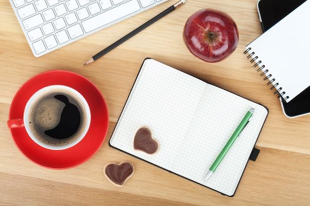 Koffiekopje, koekjes, rode appel en kantoorbenodigdheden op houten tafel