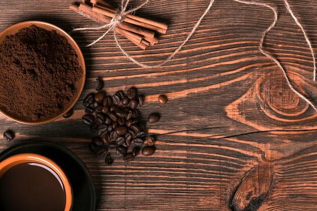 Koffiekopje, koffiebonen, gemalen koffie op houten tafel achtergrond met kaneel. bovenaanzicht. stilleven. ruimte kopiëren. plat leggen.