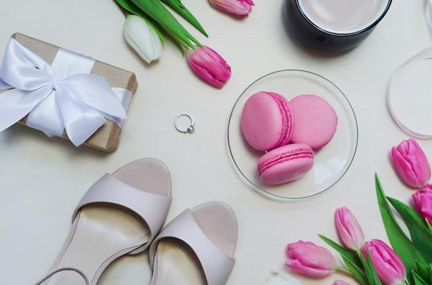 Koffiekopje, lente tulp bloemen en roze macarons op pastel tafelblad weergave verticaal.
