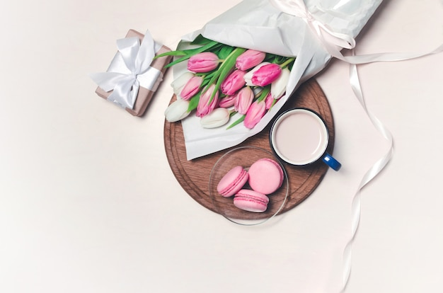 Koffiekopje, lentetulp bloemen en roze macarons op houten tafel. bovenaanzicht.