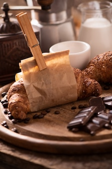Koffiekopje met een croissant en verse koffie op bruine achtergrond