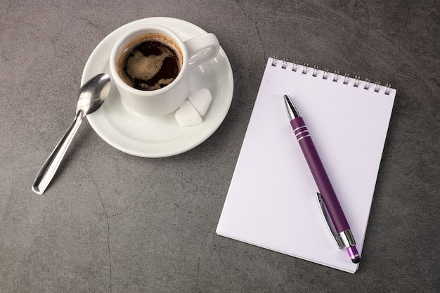 Koffiekopje met een telefoon en een notitieboekje op een donkere achtergrond