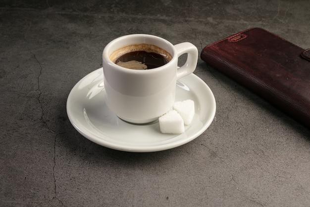 Koffiekopje met een telefoon op een donkere achtergrond