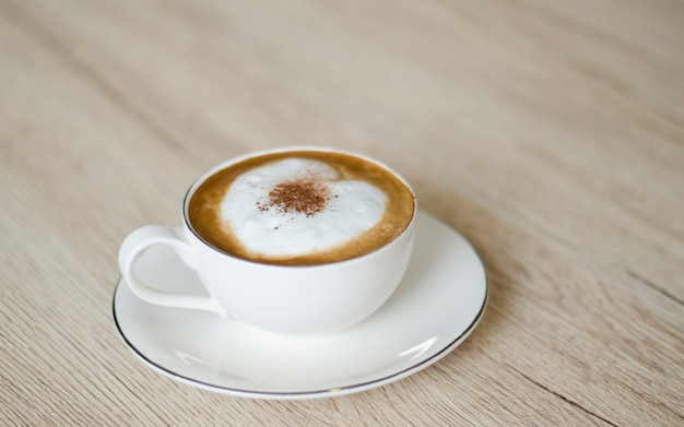 Koffiekopje met harten op oude tafel