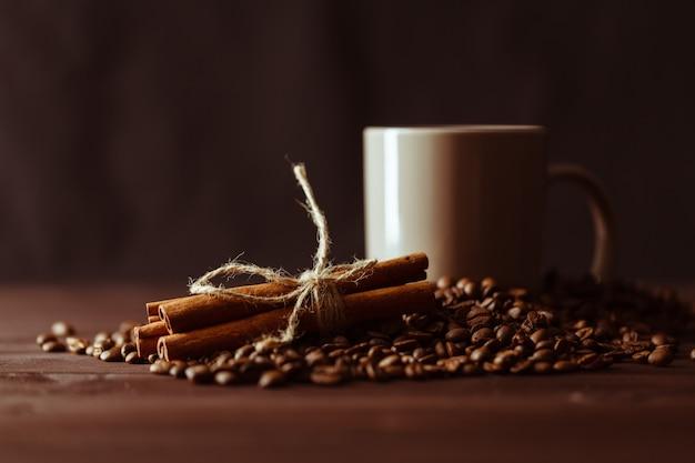 Koffiekopje met jute zak van geroosterde bonen op rustieke tafel