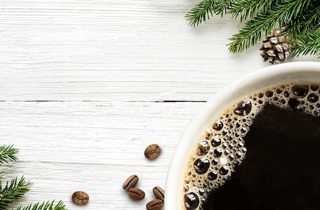 Koffiekopje met koffiebonen en kerstboomtak en kegel op witte houten achtergrond. recht boven. ruimte kopiëren