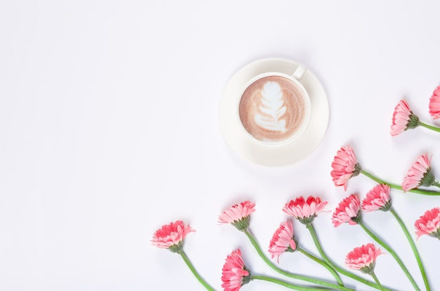 Koffiekopje met latte art met roze bloemen op witte achtergrond
